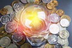 Bombilla en monedas rusas dispersadas en un fondo gris con las hojas del trébol Buena suerte, el día de St Patrick Imágenes de archivo libres de regalías