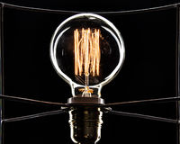 Bombilla en un fondo negro Espiral de oro Imagen de archivo