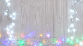 Bombillas el intermitente de lujo o guirnaldas y guirnalda en la tabla de madera por la Navidad o Años Nuevos de fondo de la deco metrajes