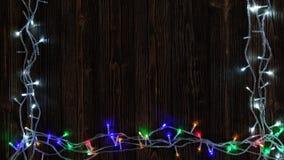 Bombillas el intermitente de lujo o guirnaldas y guirnalda en la tabla de madera por la Navidad o Años Nuevos de fondo de la deco almacen de metraje de vídeo
