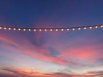 Bombillas en el alambre de la secuencia contra el cielo de la puesta del sol fotografía de archivo