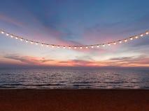 Bombillas en el alambre de la secuencia contra el cielo de la puesta del sol imágenes de archivo libres de regalías