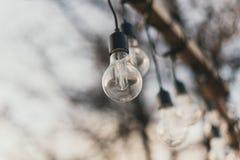 bombillas en la calle en luz del día Una guirnalda de bombillas en un pedestal de madera por la tarde en el sol al aire libre imagenes de archivo