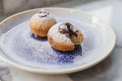 Bombolone顶视图是意大利语被填装的多福饼和被吃作为一个点心和点心与手切开 图库摄影