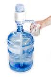 Bombona con el agua potable, la bomba de mano y un vidrio en Han de un hombre Imagen de archivo libre de regalías