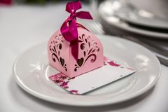 Bombonniere cor-de-rosa com uma fita lilás em uma placa branca com um cartão do convite Foto de Stock