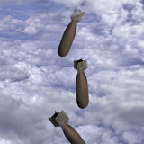 Bombs fallings through clouds Stock Photos