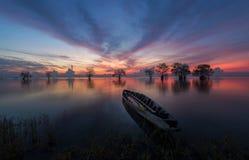 Bomen en boot in het meer met mooie hemel en wolk in vroege ochtend Stock Foto's