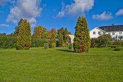 Bomen, struiken en hagen in de tuin van rood herenhuis Royalty-vrije Stock Foto's