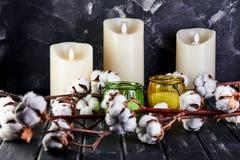 Bomullsblommor som ligger på en mörk träbakgrund och stearinljus arkivfoton