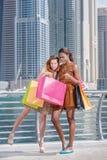 Bon achat Deux belles amies dans des robes tenant des achats Photos stock