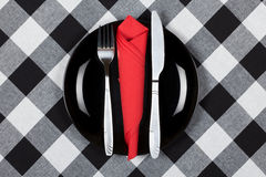 Bon apetit. Fork, knife and red napkin on black plate. Checkered black and white tablecloth Stock Images