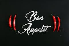 bon appetit επιγραφή και κόκκινα πιπέρια τσίλι στο Μαύρο Στοκ Εικόνες