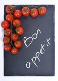 Bon appetit σε έναν πίνακα με τις ντομάτες Στοκ φωτογραφία με δικαίωμα ελεύθερης χρήσης