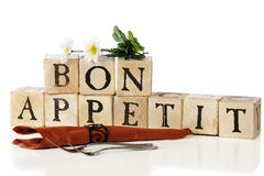 Bon Appetit. Forks, a napkin and flowers by the message, Bon Appetit, spelled out with rustic alphabet blocks. Isolated on white royalty free stock photos