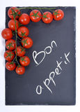 Bon appetit on a blackboard with tomatoes Royalty Free Stock Photo