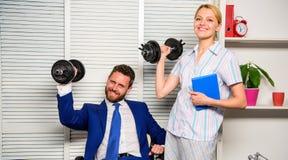 Bon concept de travail Dirigez la main d'augmenter de directeur d'homme d'affaires et de bureau avec des haltères Équipe intense  photo libre de droits