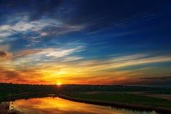 Bon coucher du soleil en nuages au-dessus de rivière Photos stock