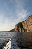 Bon Echo Cliffs. Bow of the kayak in the foreground with the sun drenched Bon Echo cliff is in northern Ontario Stock Photos