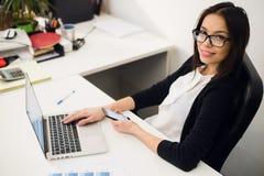 Bon entretien d'affaires Jeune belle femme gaie en verres parlant au téléphone portable et à l'aide de l'ordinateur portable avec Photos libres de droits