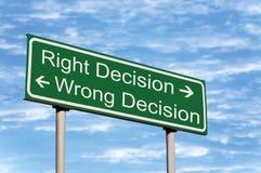 Bon signe de route faux de décision contre le ciel Photos libres de droits