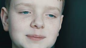 Bon visage gai sincère de bébé du garçon blond aux yeux bleus avec des taches de rousseur qui sourit à l'appareil-photo clips vidéos