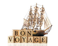 Bon Voyage. A big sailing ship behind rustic alphabet blocks arranged to say Bon Voyage.)  Isolated on white Stock Photos