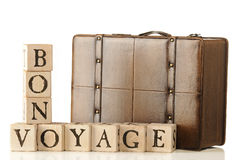 Bon Voyage. A leather suitcase sitting behind rustic alphabet blocks that are arranged to say, Bon Voyage.  Isolated on white Stock Photo