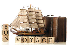 Bon Voyage. A brown leather suitcase and model tall ship by rustic alphabet blocks arranged to spell out Bon Voyage.  Isolated on white Stock Photos