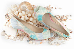 Bon voyage!. Pair of fashionable female shoes with sea-shells isolated over white Stock Images