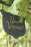 Bon Voyage sign. Cast iron bon voyage sign with grapeleaves against white wall in summer Stock Photo