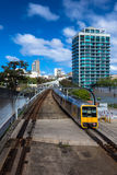 Bon voyage! train travel. Moving train coming from the station driving into the CBD, Sydney NSW Australia. Yellow train, blue sky and building make for a Royalty Free Stock Photography
