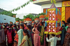 BONALU_ THE FESTIVAL OF MOTHER CULT. A group of rural children holding a decorated structure made of coloured paper in front of the village women standing with Stock Photography