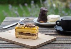 Bonbon backt auf rustikalem Schreibtisch mit Tasse Kaffee im Garten zusammen Stockfoto