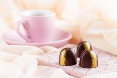 Bonbon di lusso con la tazza di caffè sul fondo di rosa pastello immagine stock