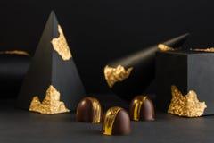 Bonbon di lusso dipinti con oro su fondo nero fotografia stock libera da diritti