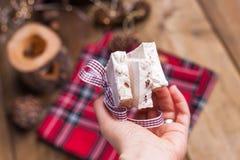 Bonbon italien traditionnel de nougat et d'amande pour Noël Sucrerie dans une main femelle L'espace libre pour le texte photographie stock libre de droits