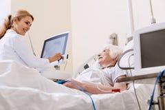 Bonbon qualifizierte Doktor, der mit ihrem hellen Patienten spricht Lizenzfreie Stockfotos