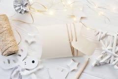 Bonbonniere för kort för modelljulhälsning och bästa sikt för etikett som är flatlay på en vit träbakgrund med en girland Arkivbild