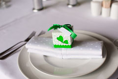 Bonbonniere on a napkin. Bonbonniere with green tape and heart on the side on plate on wedding table Royalty Free Stock Photos