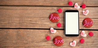 Bonbons à amour autour d'un smartphone Photos libres de droits
