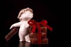 Bonbons à chocolat avec l'ange rouge de ruban et de porcelaine sur le CCB de noir Photos libres de droits