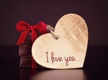 Bonbons à chocolat avec le ruban rouge et le coeur en bois du ` s de Valentine pour le jour du ` s de St Valentine Images stock