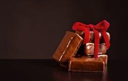 Bonbons à chocolat avec le ruban rouge sur le fond foncé pour le jour du ` s de Valentine Photo stock
