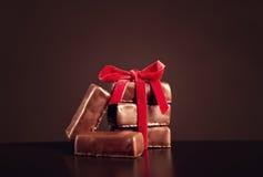 Bonbons à chocolat avec le ruban rouge sur le fond foncé pour le jour du ` s de Valentine Image libre de droits