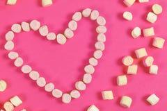 Bonbons à guimauve placés dans la forme de coeur jour du ` s de valentine et concept d'amour sur le fond rose Photos libres de droits