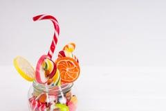 Bonbons à mâcher, lucettes lumineuses avec la canne de sucrerie et candi de gelée Photographie stock libre de droits