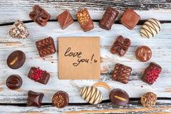 Bonbons au chocolat assortis sur le fond en bois Images libres de droits