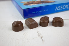 Bonbons au chocolat avec la boîte bleue à chocolat sur le bois blanc Photos libres de droits