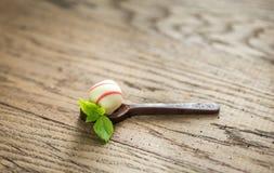 Bonbons au chocolat blancs dans la cuillère foncée de chocolat Photo stock